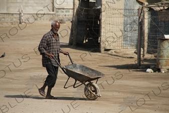 Man Pushing a Wheelbarrow along a Street in Massawa