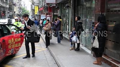 People Waiting at a Bus Stop in Macau